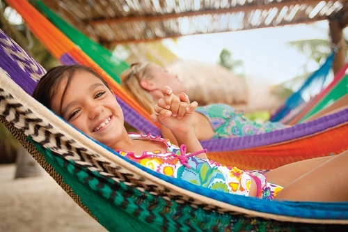 little girl smiling as she relaxes on a hammock in cozumel
