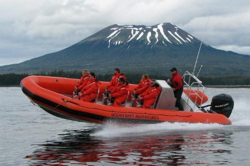 group of 7 people exploring the volcano coast on an orange ocean raft