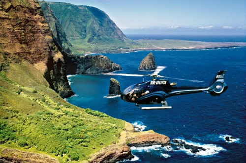 blue helicopter flying towards the green island of maui