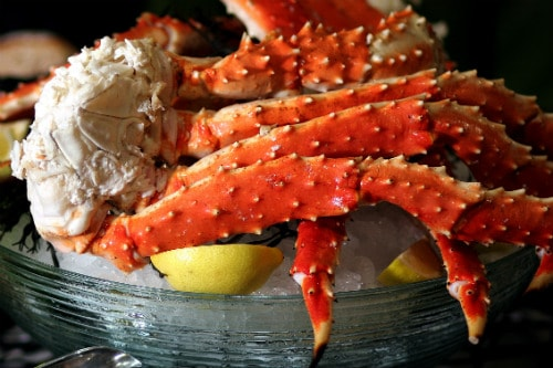 alaskan king crab legs served on ice bucket with lemon