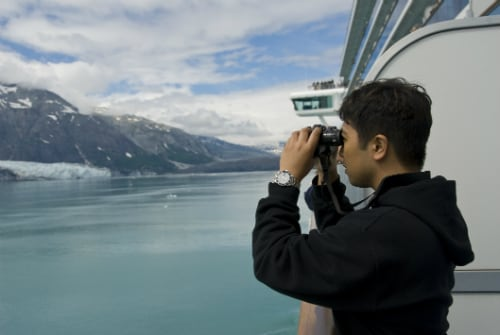 man wearing a black sweater looking at the natural beauty of alaska through binoculars on a cruise balcony