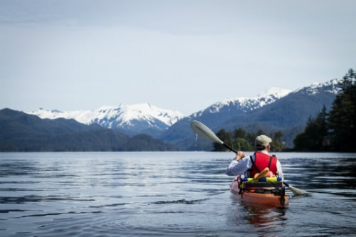 man kayaking off the shore of sitka alaska with a snow capped mountain in the background