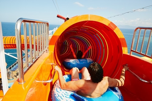 woman sliding down waterslide on an inflatable tube as a man waits his turn