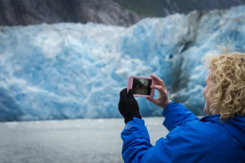 woman wearing blue jacket, taking a picture of glaciers through her pink smart phone