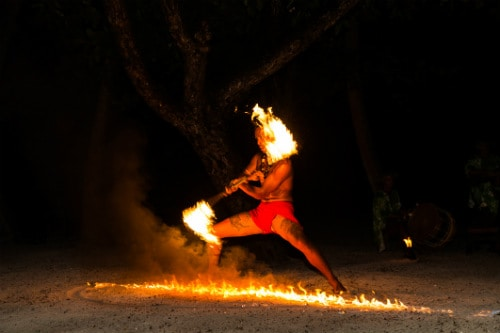 man with no shirt and a fire stick dancing a traditional hawaiian luau