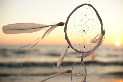 white dream catcher blowing by an ocean breeze during a sunset
