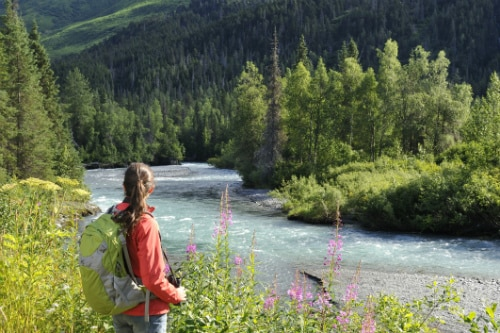 woman wearing a red jacket, hiking near a river in the alaskan forest
