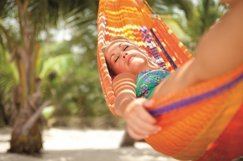 woman relaxing on an orange hammock during her stay in an oceanfront cabana