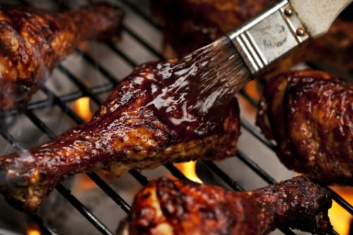 adding bbq on a chicken leg as it's cooked on a grill