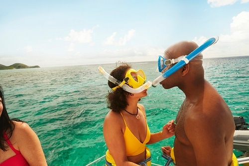 couple facing each other as the wear snorkeling gear before a caribbean excursion