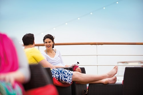 couple relaxing on the deck of a carnival ship