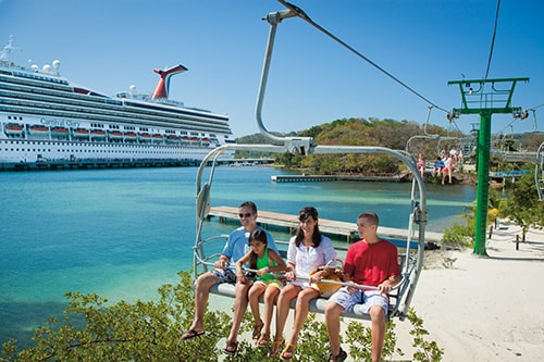 family of 4 going up a chair lift in the caribbean with carnival glory in the background