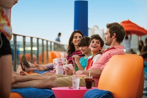 family relaxing on the ship deck as they watch a movie on the seaside theater