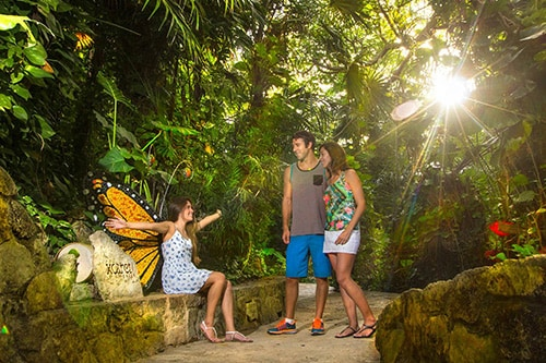 girl sitting behind butterfly wings in xcaret park as her parents look on