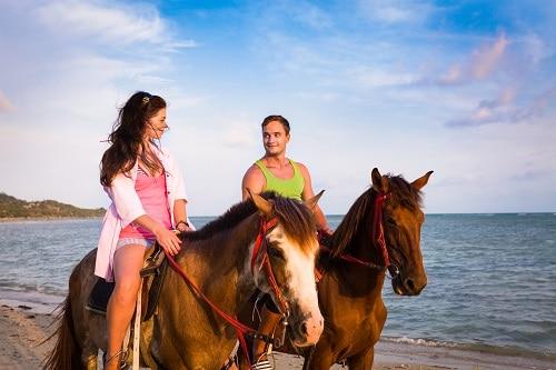 couple horseback riding on the amelia island beach during the sunset