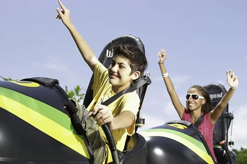 little boy and girl raising their hands as they go down a bobsled in montego bay