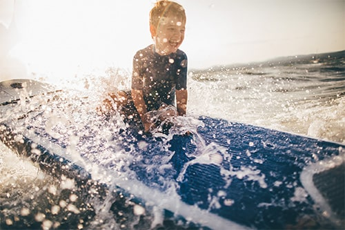 little boy surfing the ocean in san juan