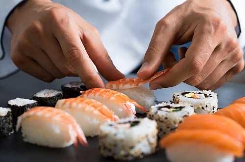 man preparing japanese sushi rolls in a seattle restaurant