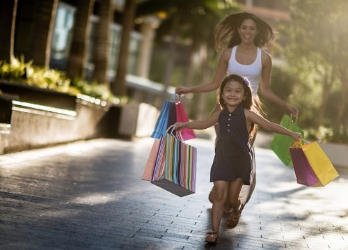 mother and daughter running down a jacksonville street holding shopping bags