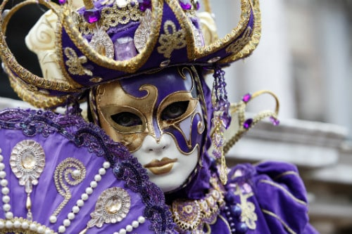 purple and white venetian mask worn during mardi gras