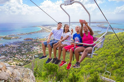 siblings taking a selfie as the go up sky explorer in st maarten