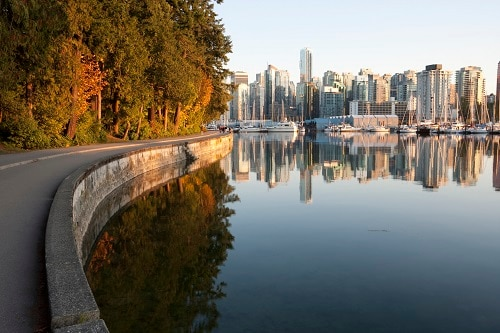 people walking along a side street in stanley park, overlooking the vancouver skyline