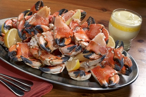 black plate of stone crabs served with lemons and tartar sauce from a tampa restaurant