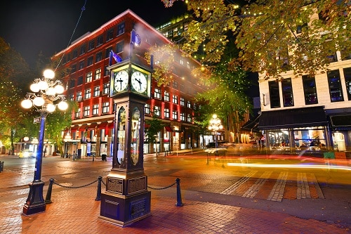 view of a local street clock in gastown in vancouver during the night