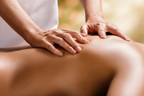 therapist massaging the back of a woman in cloud 9 spa