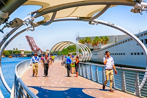 locals walking across the tampa riverwalk during the afternoon