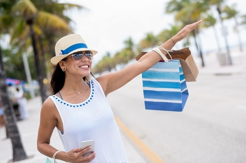 woman stopping a taxi as she shops near a beach in tampa