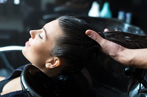 woman washing her hair in the onboard beauty salon on a carnival ship