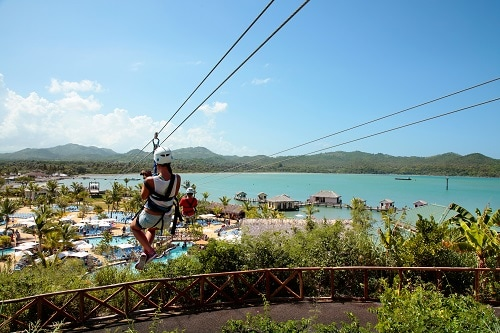 woman ziplining over the private port of amber cove