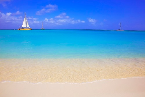 3 yachts sailing pass the sky blue waters of love beach in nassau bahamas