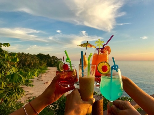 4 friends holding up their cocktails in a caribbean beach as the sunsets