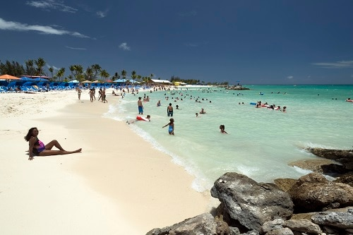 visitors sun bathing and swimming in the ocean in princess cays bahamas