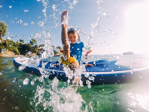 little boy on a paddle board splashing water in a caribbean private island