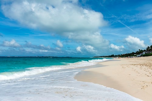 blue ocean waves hitting the white sands of cabbage beach in nassau bahamas