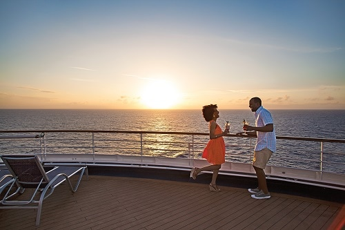 couple dancing on the deck of a carnival ship as the sun sets