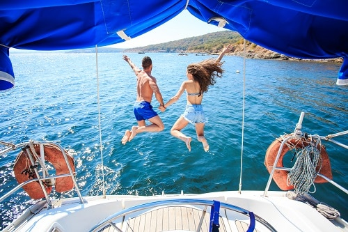 couple jumping off of a sail boat in to the water in the caribbean