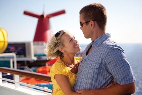 couple looking at each other on the deck of a carnival cruise ship