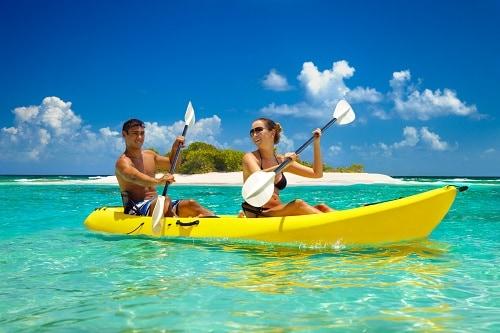 couple kayaking in hawaii on a large, 2-seater kayak
