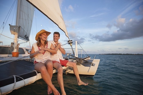 couple laughing as they explore hawaii's seas on a catamaran