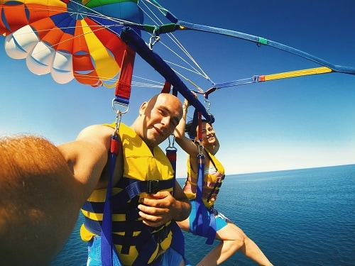 couple taking a selfie as the parasail in hawaii