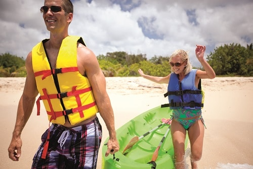 couple pulling a green kayak across the beach in cozumel mexico