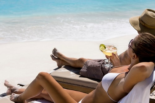 couple laying on beach chairs enjoying the beautiful caribbean sea with cocktails on hand
