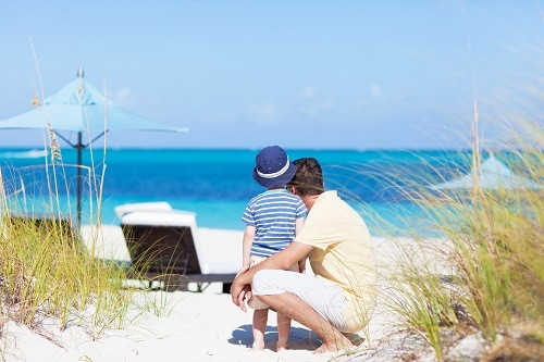 father and son staring at the crystal blue waters of fortune beach in freeport bahamas