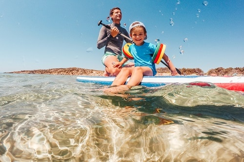 father and son paddle boarding near a beach in hawaii