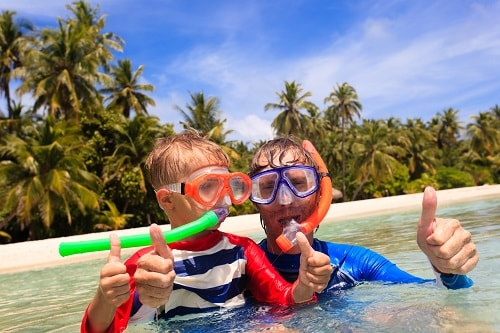 father and son holding their thumbs up as they snorkel in the bahamas