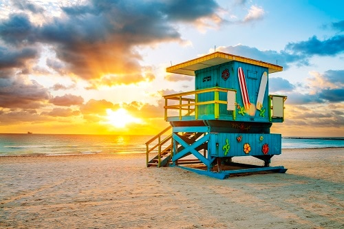 the sun setting on a lifeguard tower in miami beach